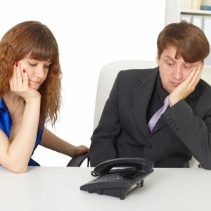 man and woman in office waiting for the phone to ring